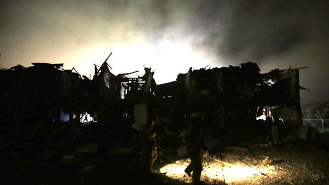 Firefighters us flashlights to search a destroyed apartment complex near a fertilizer plant that exploded earlier in West, Texas, in this photo made early Thursday morning, April 18, 2013.  (AP Photo/LM Otero)