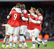 Arsenal's striker Lukas Podolski celebrates scoring a goal with teammates during their English Premier League football match against Stoke City at the Emirates Stadium in North London, England on Febuary 2, 2013. Arsenal won 1-0