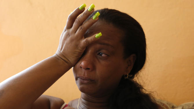 "In this March 3, 2015 photo, Melba Rosa Bacallao, mother of Cuban baseball player Yasmany Tomas, is overcome by emotion as she talks about her son during an interview at her home in Havana, Cuba. ""I miss him so much. It's tough,"" said Rosita, her voice cracking as she sifts through the pages of an album with photos of Tomas playing baseball in Cuba. ""He was always a good son. The only thing that bothered me was that he was always very loud, he always raised his voice, like thunder. I hope he has lowered his voice out there."" (AP Photo/Desmond Boylan)"