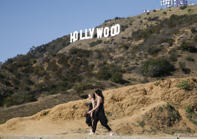 Two women hike in Griffith Park near the Hollywood sign after a plastic bag containing a human head was discovered Tuesday by two women walking their dogs on a nearby trail off Canyon Drive in Los Angeles, Wednesday, Jan. 18, 2012. Investigators have since discovered a human hand. (AP Photo/Jason Redmond)