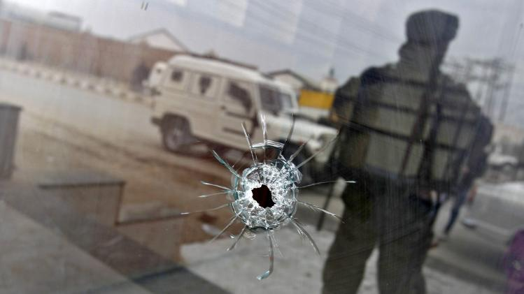 A bullet hole is seen on the glass door of a shop as an Indian army soldier stands guard after a shootout in Srinagar