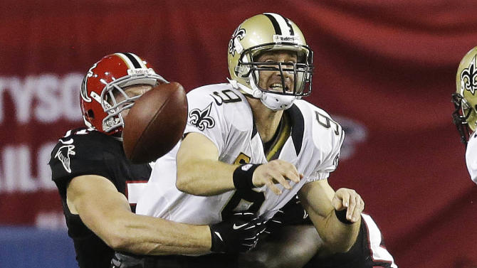 CORRECTS PLAY TO HIT, NOT SACKED - New Orleans Saints quarterback Drew Brees (9) is hit by Atlanta Falcons' Kroy Biermann (71) and Stephen Nicholas (54) during the first half of an NFL football game, Thursday, Nov. 29, 2012, in Atlanta. (AP Photo/David Goldman)
