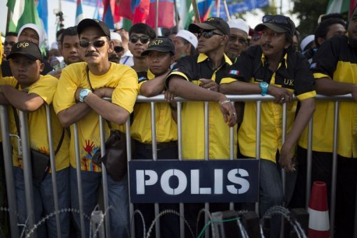 Supporters wait behind a police fence as Malaysia's opposition leader Anwar Ibrahim (unseen) submits his election nomination in Berapit on April 20, 2013. Hundreds of cases of Malaysian election violence have been reported since campaigning for tightly contested May 5 polls got under way at the weekend, police were quoted saying on Wednesday.