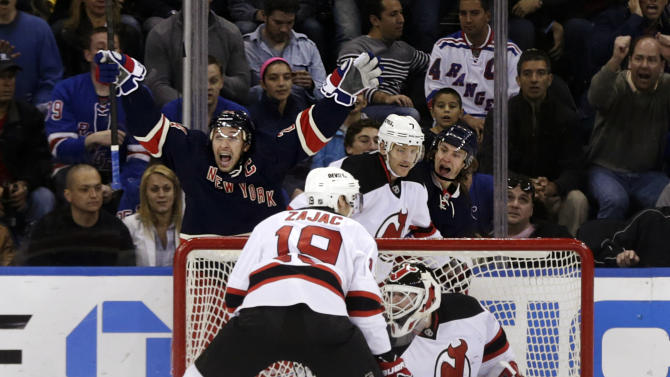 New York Rangers' Ryan Callahan, rear left, celebrates after scoring a goal on New Jersey Devils goalie Martin Brodeur, bottom, during the first period of an NHL hockey game, Sunday, April 21, 2013, in New York. (AP Photo/Seth Wenig)