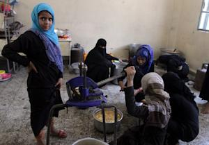 Internally displaced Yemeni women cook at a school …