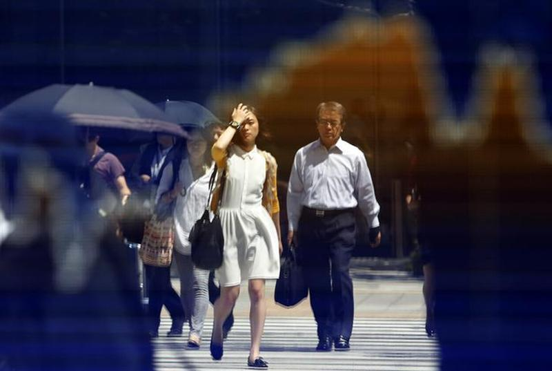 Pedestrians are reflected on a stock quotation board displaying a graph of the movement of Japan's Nikkei average outside a brokerage in Tokyo August 28, 2013.