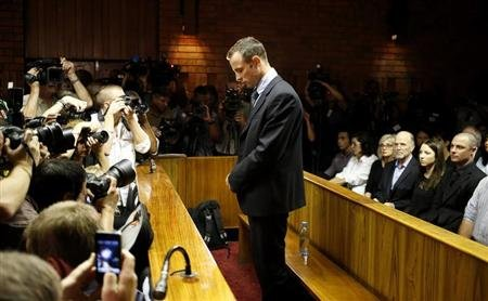 "Oscar Pistorius stands at the dock before the start of proceedings at a Pretoria magistrates court February 22, 2013. ""Blade Runner"" Pistorius, a double amputee who became one of the biggest names in world athletics, was applying for bail after being charged in court with shooting dead his girlfriend, 30-year-old model Reeva Steenkamp, in his Pretoria house. REUTERS/Mike Hutchings"