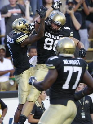 Colorado wide receiver Paul Richardson, back left, celebrates his touchdown with tight end Kyle Slavin, back right, as offensive lineman Stephane Nimbot, front, looks on against Central Arkansas in the first quarter of a college football game in Boulder, Colo., on Saturday, Sept. 7, 2013. (AP Photo/David Zalubowski)