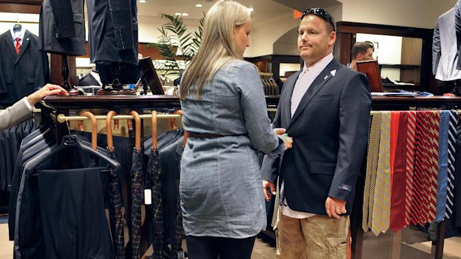In this Thursday, Sept. 20, 2012 photo, Marine Corps veteran Jared Luce of Coventry, Conn., right, is fitted with a new suit by assistant store manager Kathy Bartosiak, center, as store manager Kim Cleverdon, left, looks on at a Brooks Brothers store in West Hartford, Conn. Luce is participating in the University of Connecticut's Entrepreneurship Bootcamp for Veterans with Disabilities. More than 200,000 people are discharged from the U.S. military each year, and advocates say they often possess qualities that make good entrepreneurs: resourcefulness, a taste for risk-taking and a can-do attitude. Nonprofit groups, state governments and U.S. agencies are all providing business training aimed at giving them new purpose and easing their transition to civilian life. (AP Photo/Jessica Hill)