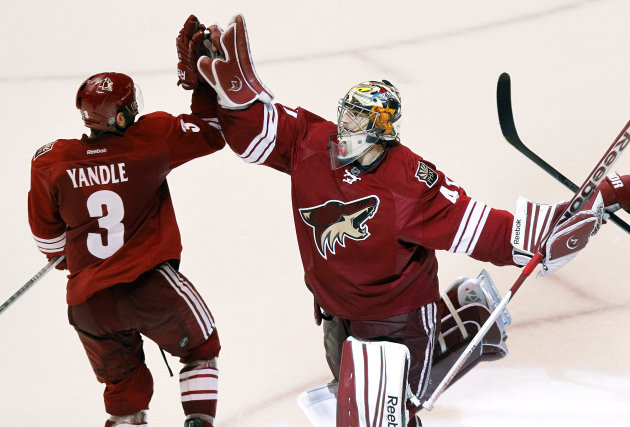 Phoenix Coyotes goalie Mike Smith, right, celebrates their 5-3 win over the Nashville Predators with Keith Yandle (3) after Game 2 in an NHL hockey Stanley Cup Western Conference semifinal playoff series, Sunday, April 29, 2012, in Glendale, Ariz. The Coyotes won 5-3. (AP Photo/Ross D. Franklin)