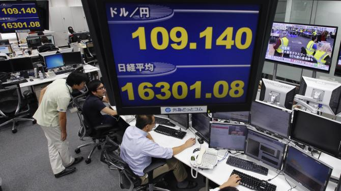 Employees of a foreign exchange trading company work under monitors in Tokyo