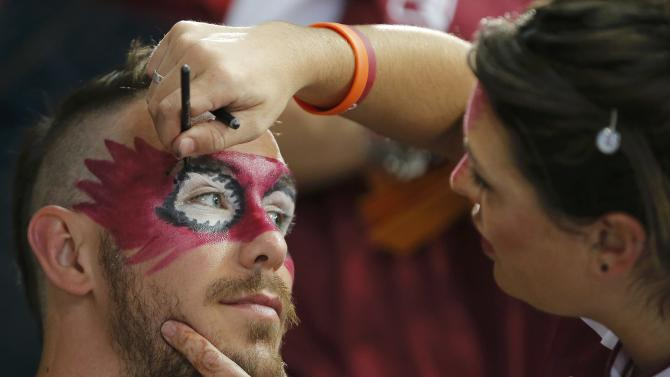 Fan of Qatar gets his face painted before their semi-final match against Poland at the 24th Men's Handball World Championship in Doha