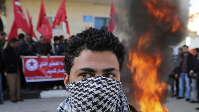 Palestinian stands near a burning tyre outside a United Nations office during a protest against the U.N. decision to suspend payments for Palestinians, in Khan Younis in the southern Gaza Strip