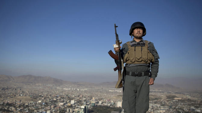 An Afghan policeman stands at attention as his commander passes by at a checkpoint overlooking Kabul, Afghanistan, Tuesday, Nov. 19, 2013. Security in the Afghan capital tightened as thousands of prominent Afghans are scheduled to meet for a Loya Jirga Nov. 21, 2013 to debate a contentious security agreement with the United States. Without the agreement the United States previously warned that it will remove all its troops by the end of 2014 and an estimated $4.1 billion promised for Afghanistan's National Security Forces would likely be rescinded. (AP Photo/Anja Niedringhaus)