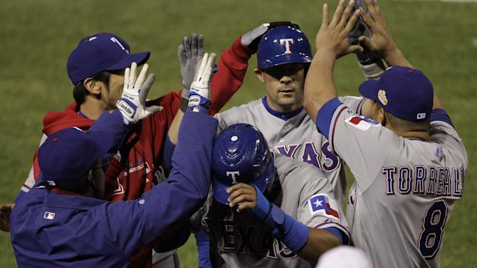Texas Rangers' Elvis Andrus, front, and Michael Young are congratulated in the dugout during the ninth inning of Game 2 of baseball's World Series against the St. Louis Cardinals Thursday, Oct. 20, 2011, in St. Louis. Andrus scored from third on a sacrifice fly by Young. (AP Photo/Paul Sancya)