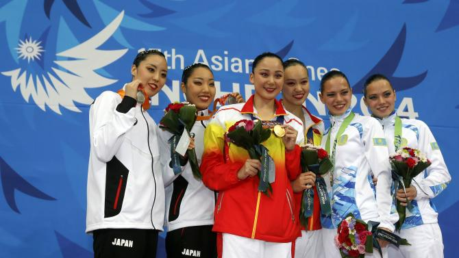 China's Huang Xuechen and Sun Wenyan pose with their gold medals after winning the women's duet synchronised swimming competition at Munhak Park Tae-hwan Aquatics Center during the 17th Asian Games in Incheon