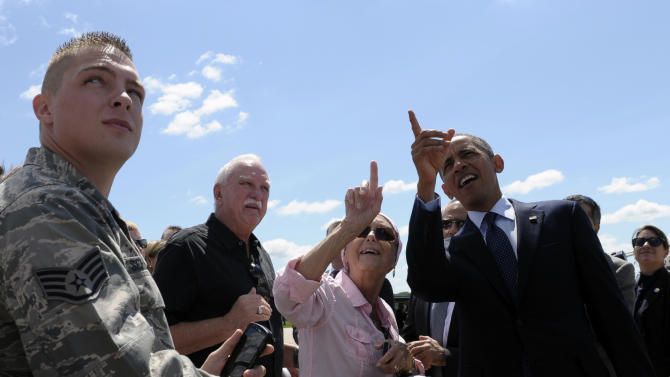 A woman points out where her son is working while President Barack Obama greets people after arriving at Quad Cities International Airport in Moline, Ill.,Wednesday, July 24, 2013. Obama is traveling to Knox College in Galesburg, Ill., to kick off a series of speeches that will lay out his vision for rebuilding the economy. (AP Photo/Susan Walsh)