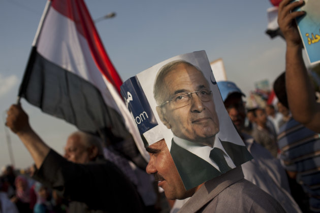 An Egyptian man wears a hand-made hat with a picture of Egyptian presidential candidate Ahmed Shafiq in Cairo, Egypt, Saturday, June 23, 2012. Egypt will release results from disputed presidential elections Sunday, the country?s top elections commission official said _ a highly anticipated announcement that will put an end to the immediate uncertainty about who is the official winner, but will almost certainly see the power struggles between Islamists, the military and other factions continue. (AP Photo/Bernat Armangue)