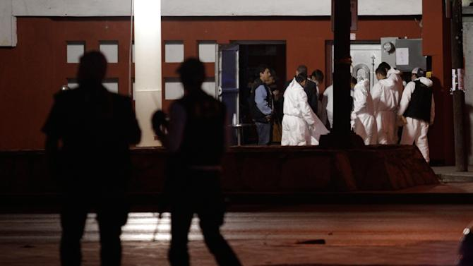 Police officers guard a crime scene as forensic technicians inspect the body of man at the entrance of a night club in Monterrey