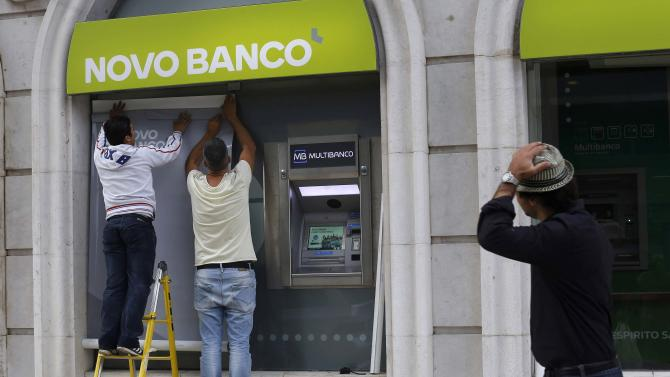 A man walks past workers installing the new logo of Portuguese Novo Banco (New Bank) at their Lisbon office