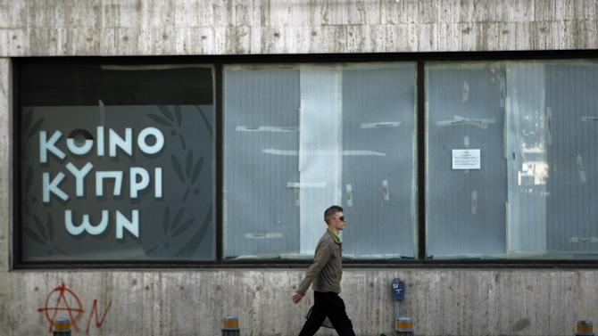 A man passes an empty closed branch of Bank of Cyprus in central capital Nicosia, Cyprus, Sunday, March 24, 2013. A top European official is leading a high-level meeting Sunday afternoon in a last-ditch effort to help Cyprus come up with a plan necessary for a 10 billion euro bailout loan that would save it from bankruptcy. (AP Photo/Petros Karadjias)