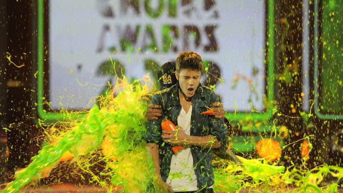 Justin Bieber gets slimed after accepting the award for favorite male singer onstage at Nickelodeon's 25th Annual Kids' Choice Awards on Saturday, March 31, 2012 in Los Angeles. (AP Photo/Chris Pizzello)