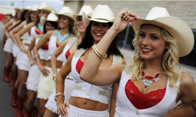 Grid girls pose for pictures after the qualifying session of the Austin F1 Grand Prix at the Circuit of the Americas in Austin