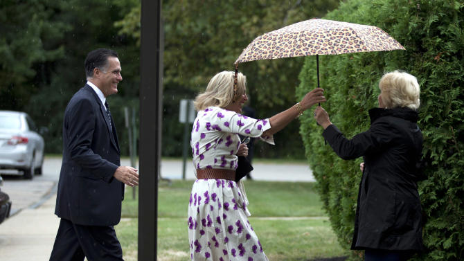 Ann Romney, center, wife of Republican presidential candidate, former Massachusetts Gov. Mitt Romney, left, is handed an umbrella by Nancy Marriott as they arrive at the Church of Jesus Christ of Latter-day Saints for services on Sunday, Sept. 2, 2012, in Wofeboro, N.H.  (AP Photo/Evan Vucci)