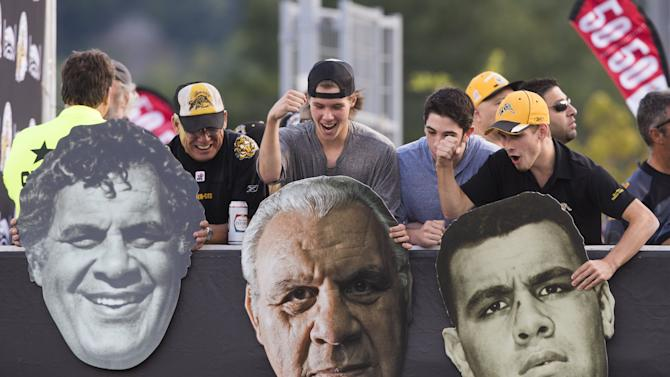 "Fans hold pictures of former Hamilton Tiger-Cats great Angelo Mosca, as the Tiger-Cats are set to retire his number ""68"" during halftime, ahead of their CFL football game against the Alouettes in Hamilton"