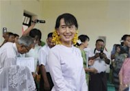Myanmar pro-democracy leader Aung San Suu Kyi smiles after presenting her expensives at the Thanlyin township election commission office on the outskirts of Yangon