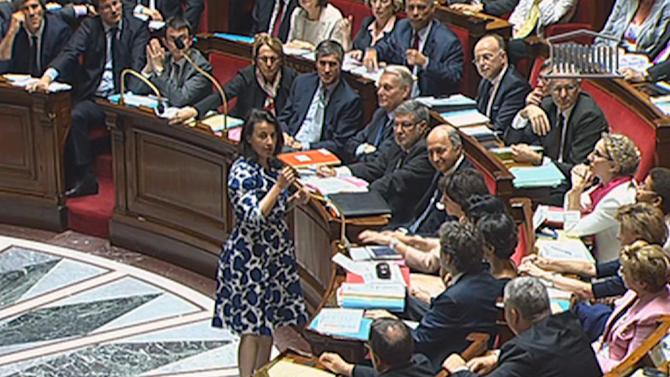 """Cecile Duflot, the Housing minister, speaks before France's National Assembly in Paris, Tuesday, July 17, 2012 in this frame made from TV.  The hooting and catcalls began as soon as the Cabinet minister stood, wearing a blue and white flowered dress. It did not cease for the entire time she spoke before France's National Assembly and the heckling came not from an unruly crowd, but from male legislators who later said they were merely showing their appreciation on a warm summer's day.   Duflot faltered very slightly, and then continued with her prepared remarks about an urban development project in Paris.  """"Ladies and gentlemen, but mostly gentlemen, obviously,"""" she said in a firm voice as hoots rang out. She completed the statement on her ministry and again sat down. None of the men in suits who preceded her got the same treatment from the deputies, and the reaction was extraordinary enough to draw television commentary and headlines for days afterward.  (AP Photo / National Assembly TV) TV OUT"""