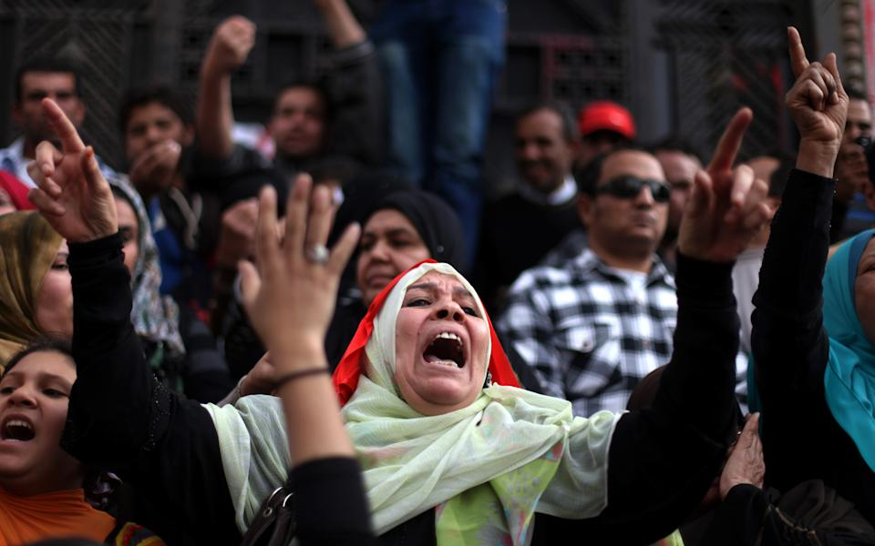 Protesters chant anti-government slogans as they demonstrate in front of Egypt's high court building in downtown Cairo, Friday, Feb. 22, 2013.  Egypt's president called multi-stage parliamentary elections beginning in April but a key opposition leader warned Friday that the vote may only inflame tensions unless there are serious political talks first.(AP Photo/Khalil Hamra)