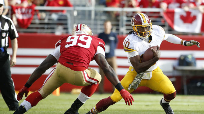 Washington Redskins quarterback Robert Griffin III (10) runs from San Francisco 49ers linebacker Aldon Smith (99) during the first quarter of an NFL football game in Santa Clara, Calif., Sunday, Nov. 23, 2014. (AP Photo/Tony Avelar)