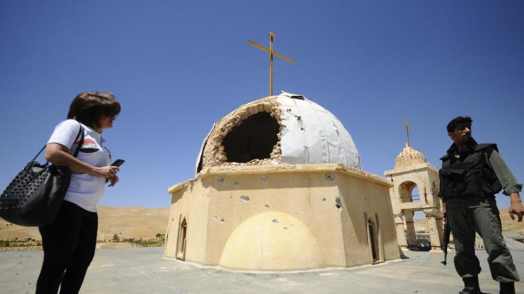 A woman and a soldier loyal to Syria's president Bashar Al-Assad stand beside a damaged church in Maaloula