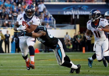 Denver Broncos' Anderson runs with the ball as he is tackled by Carolina Panthers' Thompson during the first quarter of the NFL's Super Bowl 50 football game in Santa Clara