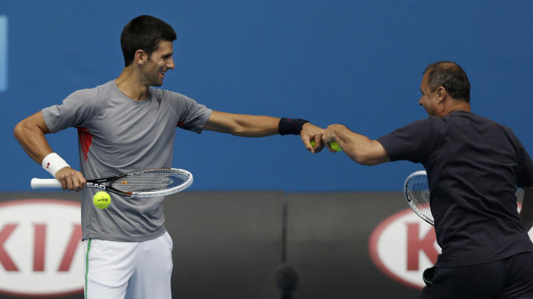 Serbia's Novak Djokovic, left, jokes with a member of his training staff during a training session at the Australian Open tennis championship in Melbourne, Australia, Sunday, Jan. 13, 2013. (AP Photo/Dita Alangkara)