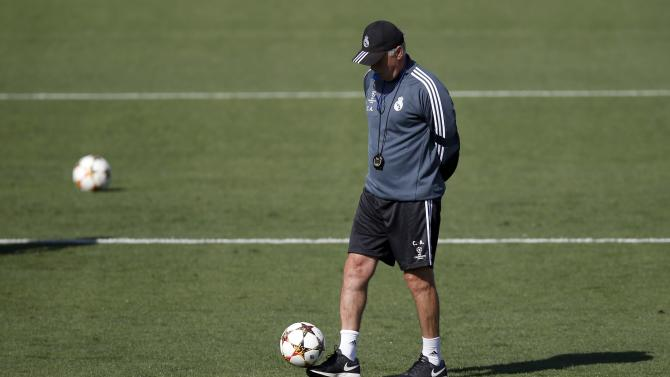 Real Madrid's coach Ancelotti walks on the pitch during their training session on the eve of their Champions League match against Basel in Madrid