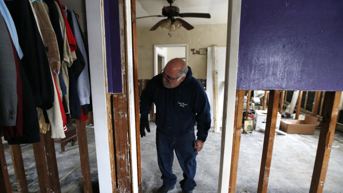 Anthony Cavallo looks at the doorway to the room of his 14-year-old daughter Amy Cavallo, where markings of growth were made throughout the years, Wednesday, Jan. 23, 2013, in Union Beach, N.J. The Cavallo's had to buy a trailer out of pocket and place it next to their home damaged by Superstorm Sandy because they've yet to receive storm aid. Cold weather is bringing extra worries to residents of the areas hit by Sandy. The deep freeze will continue into Thursday and Friday. There's a chance of snow Friday afternoon and evening, but accumulations are expected to be minor. (AP Photo/Julio Cortez)