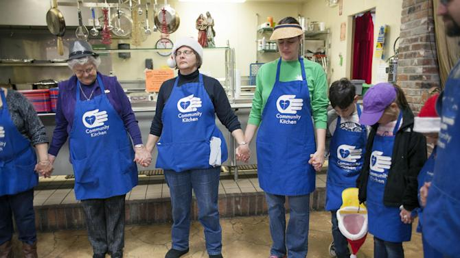 From left, Esther Meier of Bella Vista, Ark., Jan Hylko, and other volunteers gather in prayer on before serving Christmas dinner at the Community Kitchen in Paducah, Ky., Thursday, Dec. 25, 2014. (AP Photo/The Paducah Sun, John Paul Henry)