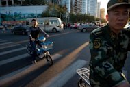 <p>People cross a traffic intersection in Beijing. Problems in the broader global economy, including Europe's prolonged debt crisis and a sluggish recovery in the US -- both major trading partners for China -- have been a drag on growth.</p>