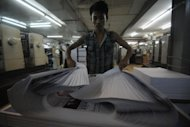 An employee checks the printed sheets of a local journal in Yangon in August. A new governing body will slowly replace the information ministry in overseeing the state press, according to Ye Naing Moe, one of the new committee's members