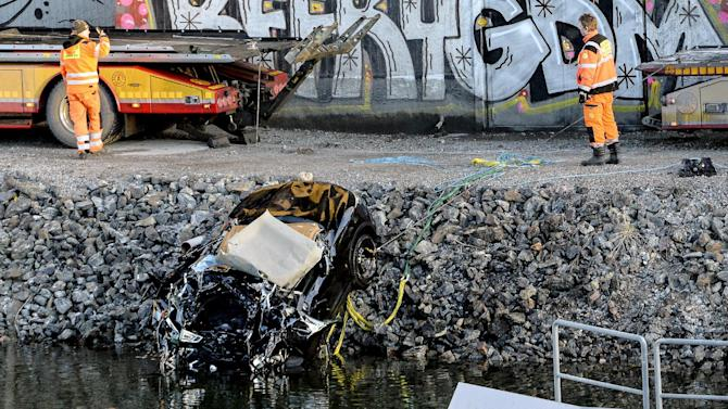 A badly damaged car is towed up from the canal under the E4 highway bridge in Sodertalje, Sweden