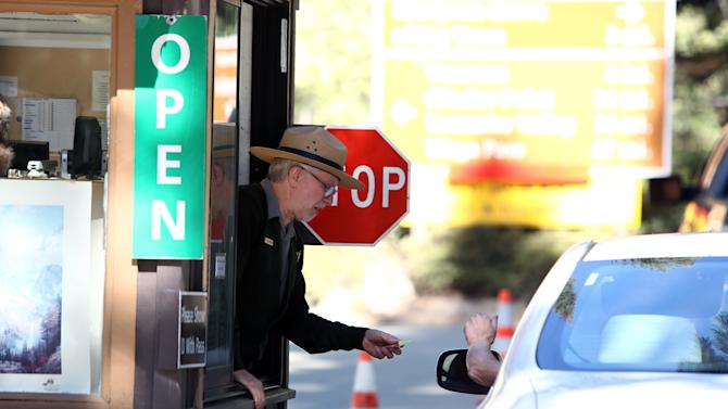 FILE - This Oct. 17, 2013 file photo shows Yosemite Park Ranger Ron Morton taking a payment from a visitor at the front gate after the reopening of Yosemite National Park, Calif. The park reopened at the end of the 16-day partial government shutdown. There is a way to prevent government shutdowns. A change in U.S. law would keep federal workers on the job and ensure that the Statue of Liberty and Yosemite stay open during a budget fight, instead of becoming political pawns. The idea's been around for three decades, but even after a 16-day shutdown that cost billions of dollars and outraged voters, it's a tough sell in Washington. Why? Without the risk of a shutdown, there's no telling how long politicians might put off making hard budget decisions. The United States could end up with government by autopilot. (AP Photo/Gary Kazanjian, File)