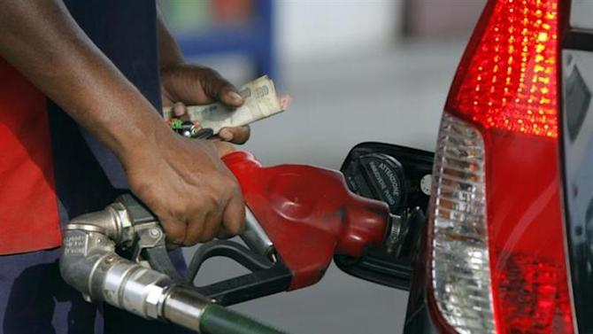 An employee fills a vehicle with fuel at a fuel station in New Delhi June 25, 2010. REUTERS/Mukesh Gupta/Files