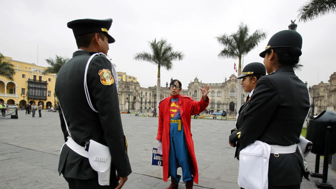 Avelino Chavez, wearing his signature Superman costume, talks with tourist police in the main square in downtown Lima, Peru, Friday, June 15, 2012. Chavez, 52, took on the Superman persona 15 years ago, when he lost his job as a security guard, and says he has had work ever since. Chavez also says he only earns about $160 US dollars per month, but that he has the strength of a superhero. Chavez currently works to promote a travel agency. (AP Photo/Martin Mejia)