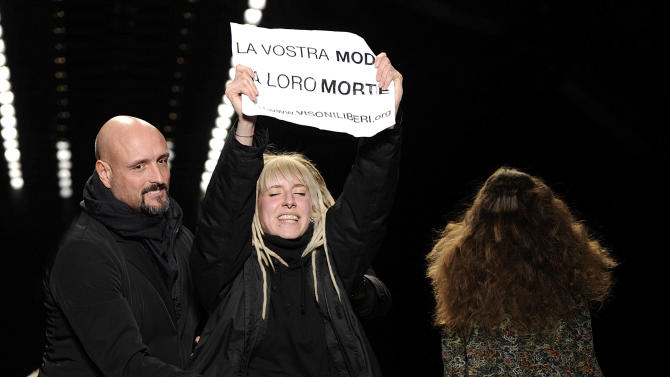 """A security guard stops an animal rights activist walking on the catwalk with a placard reading in Italian """"La vostra moda la loro morte"""" (Your fashion their death) during the show of the Just Cavalli women's Fall-Winter 2013-14 collection, part of the Milan Fashion Week, unveiled in Milan, Italy, Thursday, Feb. 21, 2013. (AP Photo/Giuseppe Aresu)"""