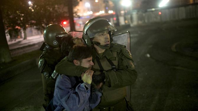 Demonstrators are detained by riot policemen during a rally against police violence  in Santiago