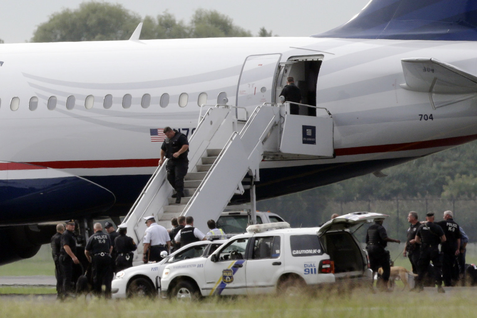 Law enforcement officials work around a US Airways flight at Philadelphia International Airport, after the plane returned to the airport, Thursday, Sept. 6, 2012, in Philadelphia. A security scare that prompted authorities to recall an airborne U.S. flight was the result of an apparent hoax, police said Thursday.