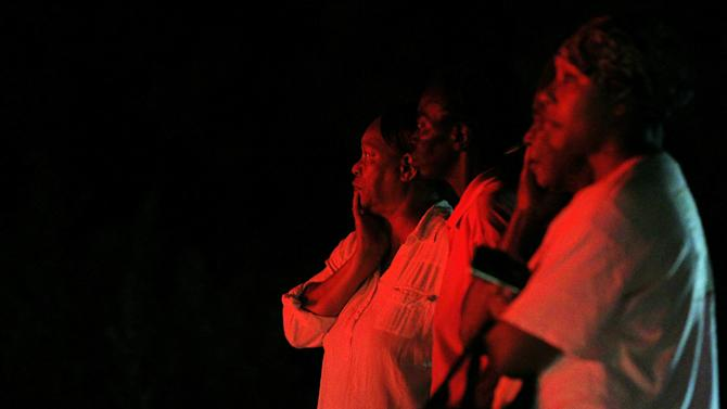 Bystanders watch as public safety personnel work at the scene of a fire at Mount Zion African Methodist Episcopal church, late Tuesday night, June 30, 2015, in Greeleyville, S.C. The African-American church, which was burned down by the Ku Klux Klan in 1995, caught fire Tuesday night. (Veasey Conway/The Morning News via AP)