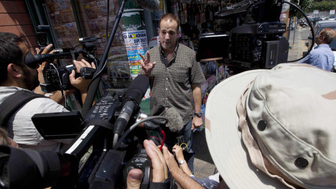 Michael Kobold, family friend of actor James Gandolfini, tells the time of a press conference which will take place later in the day as he meets the media outside the morgue of the Policlinico Umberto I hospital where the body of Gandolfini is kept, in Rome, Friday, June 21, 2013. James Gandolfini died Wednesday night after suffering a cardiac arrest while vacationing with friends and relatives in Rome. (AP Photo/Alessandra Tarantino)